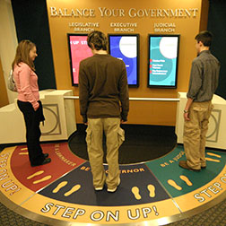 Image of older students performing a balance your government exercise with an interactive display in the Visitor Education Center.